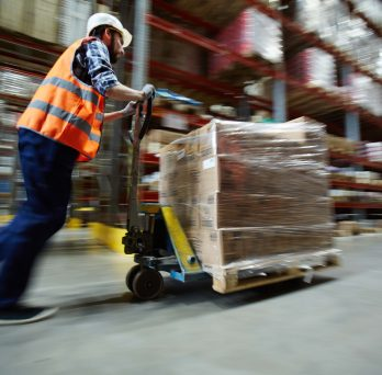 A warehouse worker pushes goods on a pallet jack